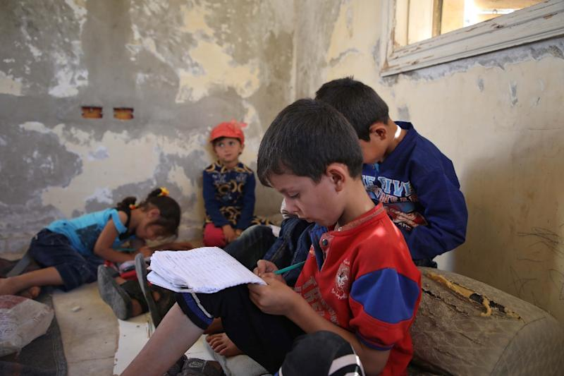 Displaced Syrian children attend class at a makeshift school in an opposition-held area in the west of the northern province of Aleppo (AFP Photo/Aaref WATAD)