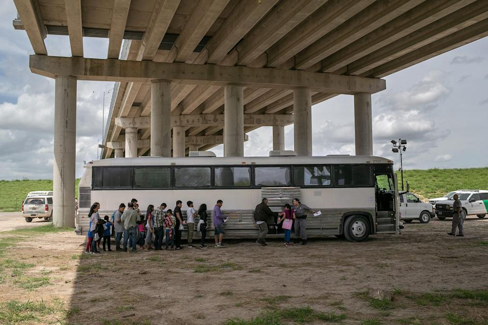 MCALLEN, TEXAS - JULY 02: Immigrants wait to be transported to a U.S. Border Patrol processing center after they were taken into custody on July 02, 2019 in McAllen, Texas. The immigrants, mostly families from Central America, turned themselves in to border agents after rafting across the Rio Grande from Mexico to seek political asylum in the United States.  (Photo by John Moore/Getty Images)