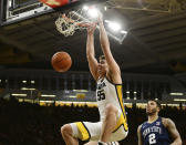 FILE - Iowa's Luka Garza (55) dunks the ball as Penn State's Myles Dread (2) looks on during the second half of an NCAA college basketball game in Iowa City, Iowa, in this Saturday, Feb. 29, 2020, file photo. Iowa will begin the college basketball season at No. 5 in the preseason AP Top 25 poll released Monday, Nov. 9, 2020.(AP Photo/Cliff Jette, File)