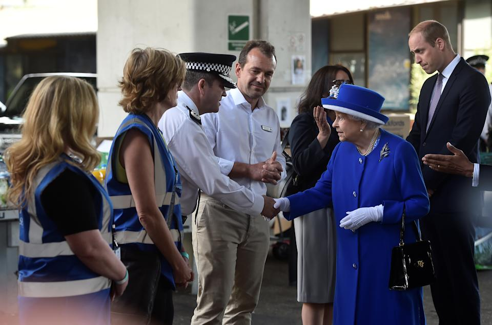 Britain's Queen Elizabeth and Prince William meet emergency workers near the scene of the the fire that destroyed the Grenfell Tower block, in north Kensington, West London, Britain June 16, 2017.  REUTERS/Hannah McKay