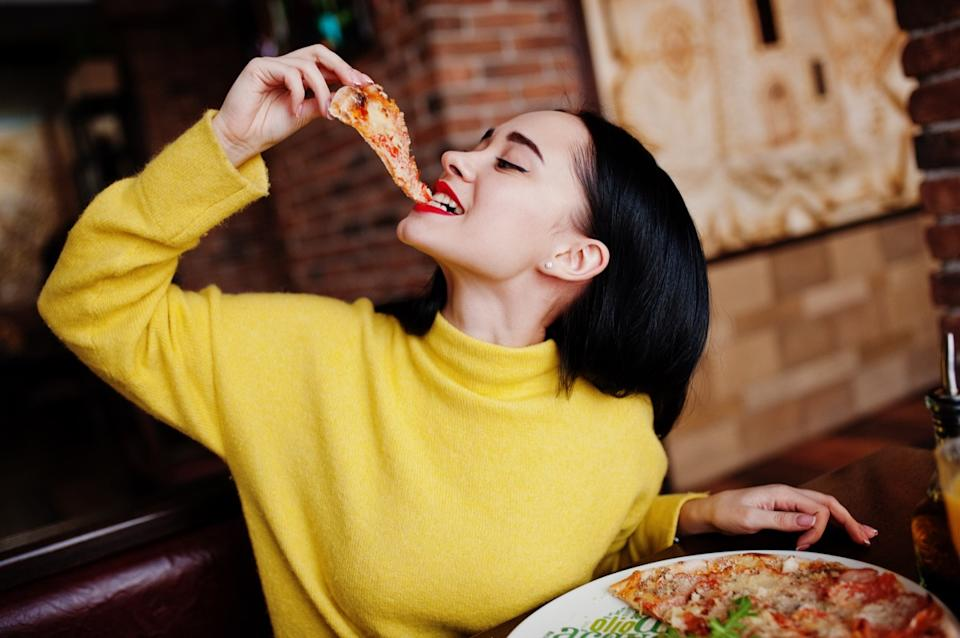 girl in yellow sweater eating pizza at restaurant