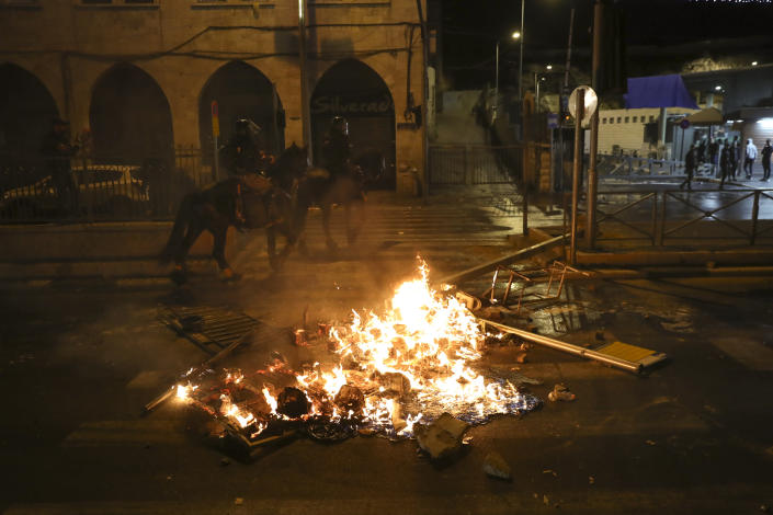 Mounted Israeli police officers ride past a fire during clashes with Palestinians, just outside Jerusalem's Old City, Thursday, April 22, 2021. Israeli police manned barricades to prevent hundreds of Jewish extremists from marching to the area as police clashed with Palestinians on a nightly basis since the start of the Muslim holy month of Ramadan last week, when they set up barricades at Damascus Gate, a traditional outdoor gathering spot. (AP Photo/Ariel Schalit)