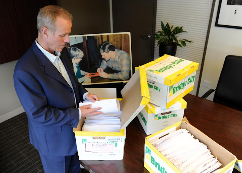 In a Tuesday, Oct., 16, 2012 photo, Portland attorney Kelly Clark examines some of the 14,500 pages of previously confidential documents created by the Boy Scouts of America concerning child sexual abuse within the organization, in preparation for releasing the documents Thursday, Oct. 18, as he stands in his office in Portland, Ore. The Boy Scouts of America fought to keep those files confidential. (AP Photo/Greg Wahl-Stephens)