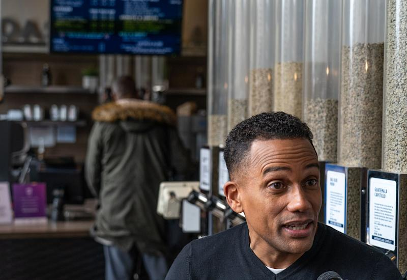"""Actor Hill Harper talks with a television reporter while doing promotion about """"Credit over Coffee"""" as part of an effort to build credit scores through a new program called Experian Boost at his business the Roasting Plant Coffee in downtown Detroit on Wednesday, May 1, 2019."""