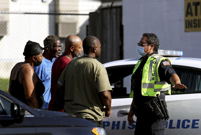 Memphis Police Department officers talk to nearby residents after a deadly shooting at a nearby post office Tuesday, Oct. 12, 2021 in the Orange Mound neighborhood of Memphis, Tenn. Police investigated a shooting Tuesday at a post office in an historic neighborhood of Memphis, Tennessee, the third high-profile shooting in the region in weeks.(Patrick Lantrip/Daily Memphian via AP)