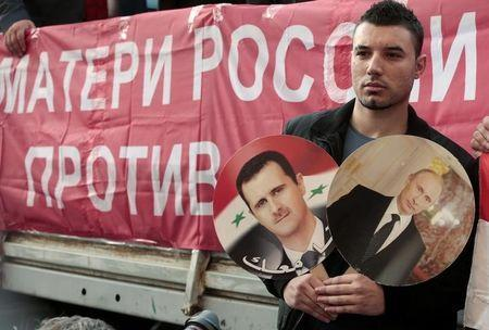 A participant hold images of Russian President Vladimir Putin and Syrian President Bashar al-Assad during an anti-war protest organised by the Communist party near the U.S. embassy in Moscow in this September 12, 2013 file photo. REUTERS/Tatyana Makeyeva