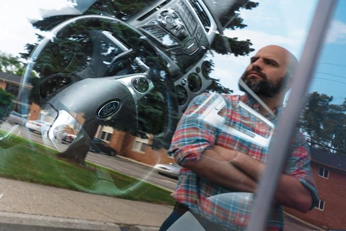 Ryan Karczewski is reflected in the driver's side window of his 2014 Ford Focus SE outside of his apartment in Royal Oak on Friday, June 28, 2019.