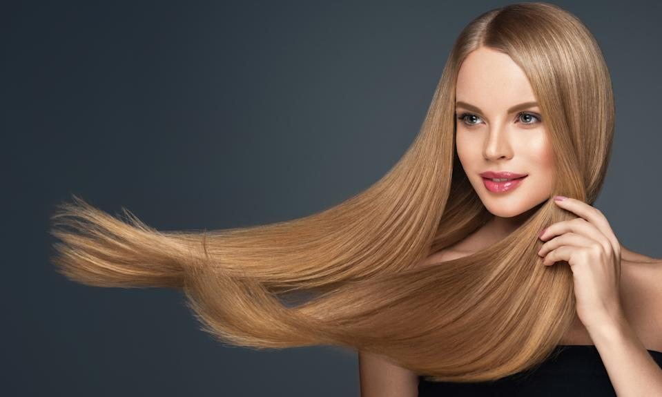 Mature blonde haired woman with voluminous, flying hairstyle. Beautiful model with long, dense, straight hair and vivid makeup with pale red lipstick. Hairdressing art, hair care and beauty products.