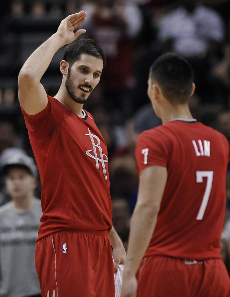 Houston Rockets forward Omri Casspi, left, of Israel, congratulates guard Jeremy Lin on a play during the second half of an NBA basketball game against the San Antonio Spurs on Wednesday, Dec. 25, 2013, in San Antonio. Houston won 111-98. (AP Photo/Darren Abate)