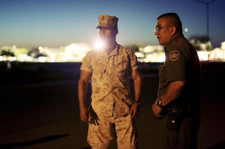 First Lt. Jose Negrete (L) and a border patrol agent speak with residents at the scene of a U.S. military jet crash in Imperial, California June 4, 2014. REUTERS/Sandy Huffaker