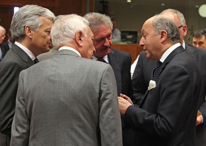 French Foreign Minister Laurent Fabius, right, talks with Belgium's Foreign Minister Didier Reynders, left, Luxembourg's Foreign Minister Jean Asselborn, second right, and Spain's Foreign Minister Jose Manuel Garcia-Margallo y Marfil, second left, during the EU foreign ministers meeting, at the European Council building in Brussels, Monday, May 27, 2013. The European Union nations remain divided on Monday whether to ease sanctions against Syria to allow for weapons shipments to rebels fighting the regime of Syria's President Bashar Assad. (AP Photo/Yves Logghe)