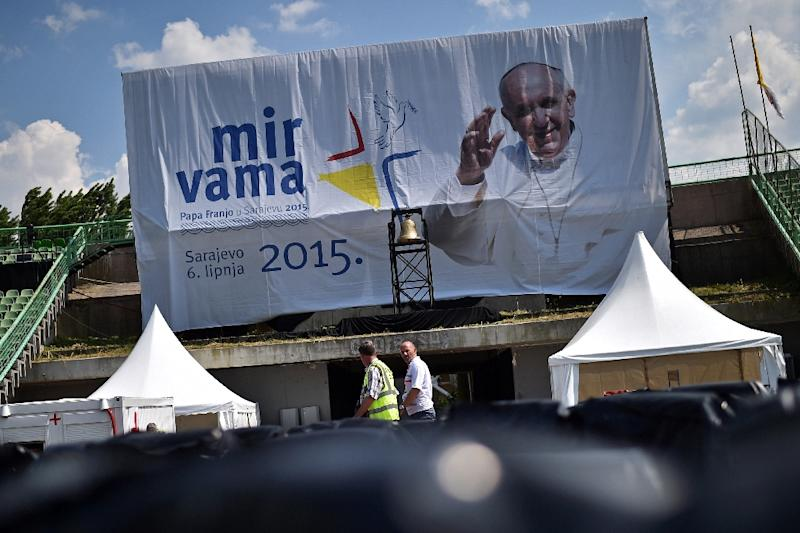 Workers walk past a banner with a picture of Pope Francis at Sarajevo city stadium on June 5, 2015 (AFP Photo/Andrej Isakovic)