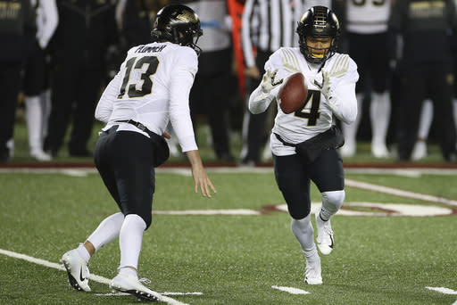 Purdue wide receiver Rondale Moore (4) receives the ball from quarterback Jack Plummer (13) during the first half of the team's NCAA college football game against Minnesota, Friday, Nov. 20, 2020, in Minneapolis. (AP Photo/Stacy Bengs)