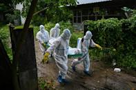 Volunteers carry the body of a coronavirus victim to a cemetery in Hle Guu