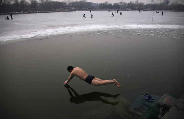 A swimmer dives into the icy water of the Houhai Lake in central Beijing, February 16, 2013. REUTERS/Petar Kujundzic (CHINA - Tags: SOCIETY ENVIRONMENT TPX IMAGES OF THE DAY) - RTR3DV01