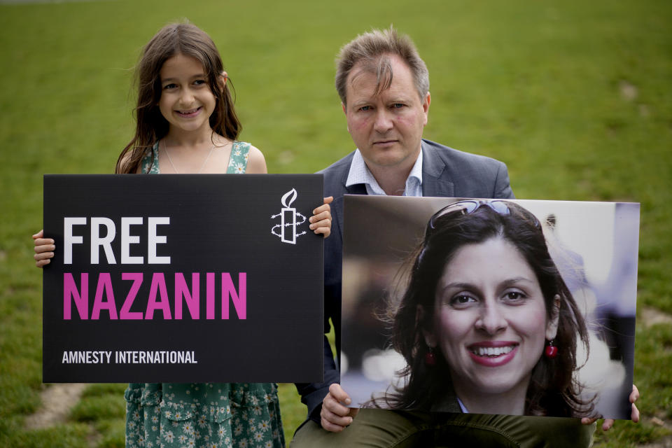 Richard Ratcliffe, the husband of imprisoned British-Iranian Nazanin Zaghari-Ratcliffe and their seven year old daughter Gabriella pose for the media backdropped by the scaffolded Houses of Parliament and the Elizabeth Tower, known as Big Ben, in Parliament Square, London, to mark the 2,000 days she has been detained in Iran, Thursday, Sept. 23, 2021. Zaghari-Ratcliffe was originally sentenced to five years in prison after being convicted of plotting the overthrow of Iran's government, a charge that she, her supporters and rights groups deny. While employed at the Thomson Reuters Foundation, the charitable arm of the news agency, she was taken into custody at the Tehran airport in April 2016 as she was returning home to Britain after visiting family. (AP Photo/Matt Dunham)