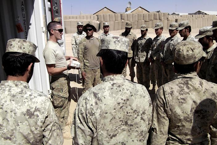 This photo taken Oct. 10, 2012 shows a U.S. soldier instructing Afghan National Civil Order Police (ANCOP) in emergency medical treatment at Forward Operating Base Warrior, in Gelan district, Ghazni province, Afghanistan. (AP Photo/Robert Burns)