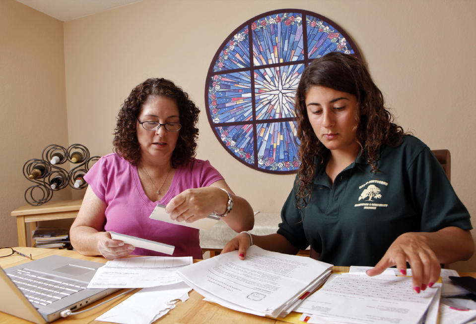 In this Aug. 19, 2009 photo, Veronica McGregor, left, and her daughter, Katie McGregor, 16, look over pay stubs and other financial information pertaining to Katie's first summer job as a swimming teacher at Hawthorne city pool, at their home in Redondo Beach, Calif. (AP Photo/Damian Dovarganes)