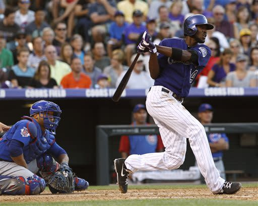 Colorado Rockies' Dexter Fowler, right, follows the flight of his triple to drive in two runs as Chicago Cubs catcher Wellington Castillo looks on in the fourth inning of a baseball game in Denver on Saturday, July 20, 2013, in Denver. (AP Photo/David Zalubowski)