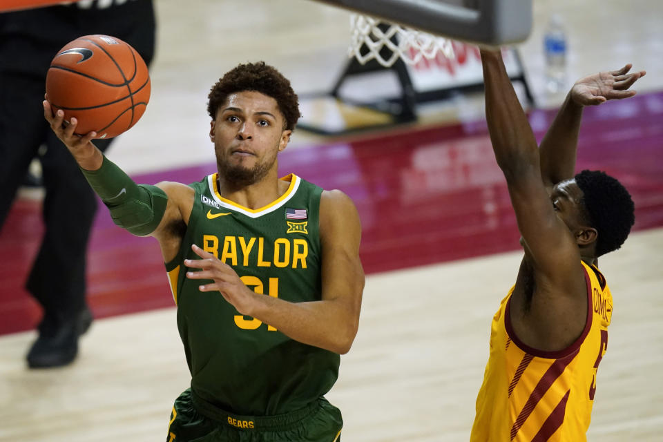 FILE - In this Saturday, Jan. 2, 2021, file photo, Baylor guard MaCio Teague drives to the basket ahead of Iowa State guard Jalen Coleman-Lands, right, during the second half of an NCAA college basketball game in Ames, Iowa. There really are no tougher matchups for Baylor guards Jared Butler, Davion Mitchell and MaCio Teague than in those countless hours they spend in the gym going 1-on-1 against each other. Or for opposing teams when that trio of guards is on the court together for the Bears, the Big 12 champions and a No. 1 seed in the NCAA Tournament for the first time. (AP Photo/Charlie Neibergall, File)