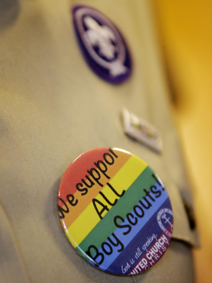 "Former Cub Scouts den leader Jennifer Tyrrell, who was ousted from Scouting because she is openly gay, wears a button on her uniform shirt that reads ""We Support All Boy Scouts"" as she responds to a reporters question Thursday, May 23, 2013, in Grapevine, Texas. Local leaders of the Boy Scouts of America voted Thursday to ease a divisive ban and allow openly gay boys to be accepted into the nation's leading youth organization — one of the most dramatic moves the organization has made in a century. (AP Photo/Tony Gutierrez)"