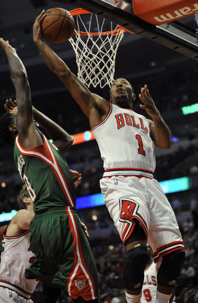 Chicago Bulls' Derrick Rose (1), goes up for a shot against Milwaukee Bucks' Larry Sanders (8), during the first half of an NBA preseason basketball game in Chicago, Monday, Oct. 21, 2013. (AP Photo/Paul Beaty)