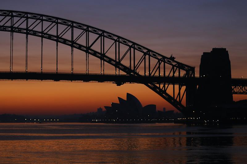 The Sydney Opera House and the Sydney Harbour Bridge with an orange hue at dawn.