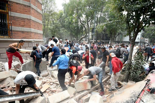 People remove debris of a damaged building.