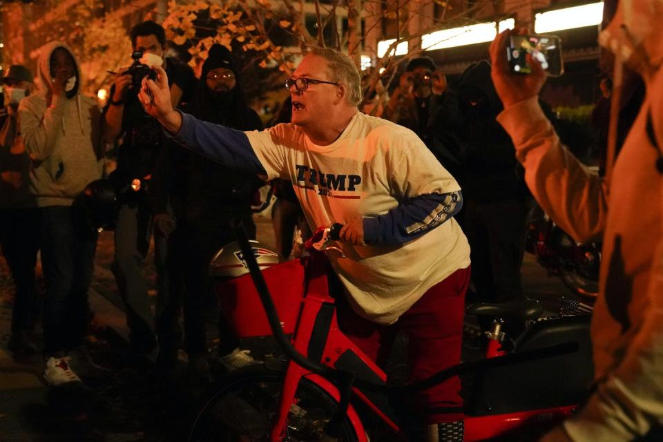 A man on a bicycle in a Trump T-shirt sprays something at someone standing nearby