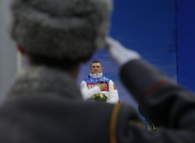 A Russian honor guard soldier salutes as Roman Petushkov of Russia, winner of the men's biathlon, 7.5km sitting event listens to the Russian national anthem during medal ceremony at the 2014 Winter Paralympic, Saturday, March 8, 2014, in Krasnaya Polyana, Russia. (AP Photo/Dmitry Lovetsky)