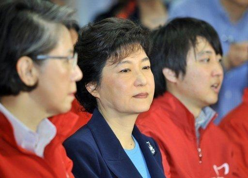 Park Geun-Hye (C), interim leader and likely presidential candidate of the conservative New Frontier Party, and candidates of the party watch TV screens showing the result of exit polls for the National Assembly elections in Seoul, in April 2012