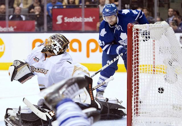 Toronto Maple Leafs forward Phil Kessel, right, scores past Anaheim Ducks goalie Jonas Hiller, left, during the second period of an NHL hockey game in Toronto on Tuesday, Oct. 22, 2013. (AP Photo/The Canadian Press, Nathan Denette)