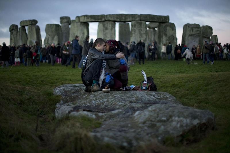 FILE - People embrace by the ancient stone circle of Stonehenge, in southern England, as access to the site is given to druids, New Age followers and members of the public on the annual Winter Solstice, in this Friday, Dec. 21, 2012 file photo. British researchers have proposed a new theory for the origins of Stonehenge: It may have started as a giant burial ground for elite families around 3,000 B.C.  New studies of cremated human remains excavated from the site suggest that some 500 years before the Stonehenge we know today was built, a larger stone circle was erected at the same site as a community graveyard, researchers said Saturday March 9 2013. (AP Photo/Matt Dunham, File)