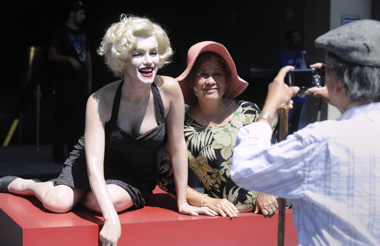 A tourist poses for a picture with a likeness of Marilyn Monroe in Hollywood Phil McCarten / Reuters