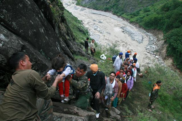 Indian army officials help travellers and villagers up a steep slope after they were stranded by the rising floodwaters of the River Alaknanda near Govindghat, Chamoli District in the northern Indian state of Uttarakhand on June 18, 2013. Military helicopters have carried out emergency food drops June 19, for thousands of people stranded by flash flooding from early monsoon rains which has killed at least 120 in northern India, officials said. AFP PHOTO/STR