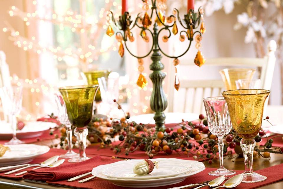 <p>A candelabra is one of the easiest ways to add a sophisticated flair to an autumn dinner table. Rest one on a bed of berry branches to make even more of an impact. </p>