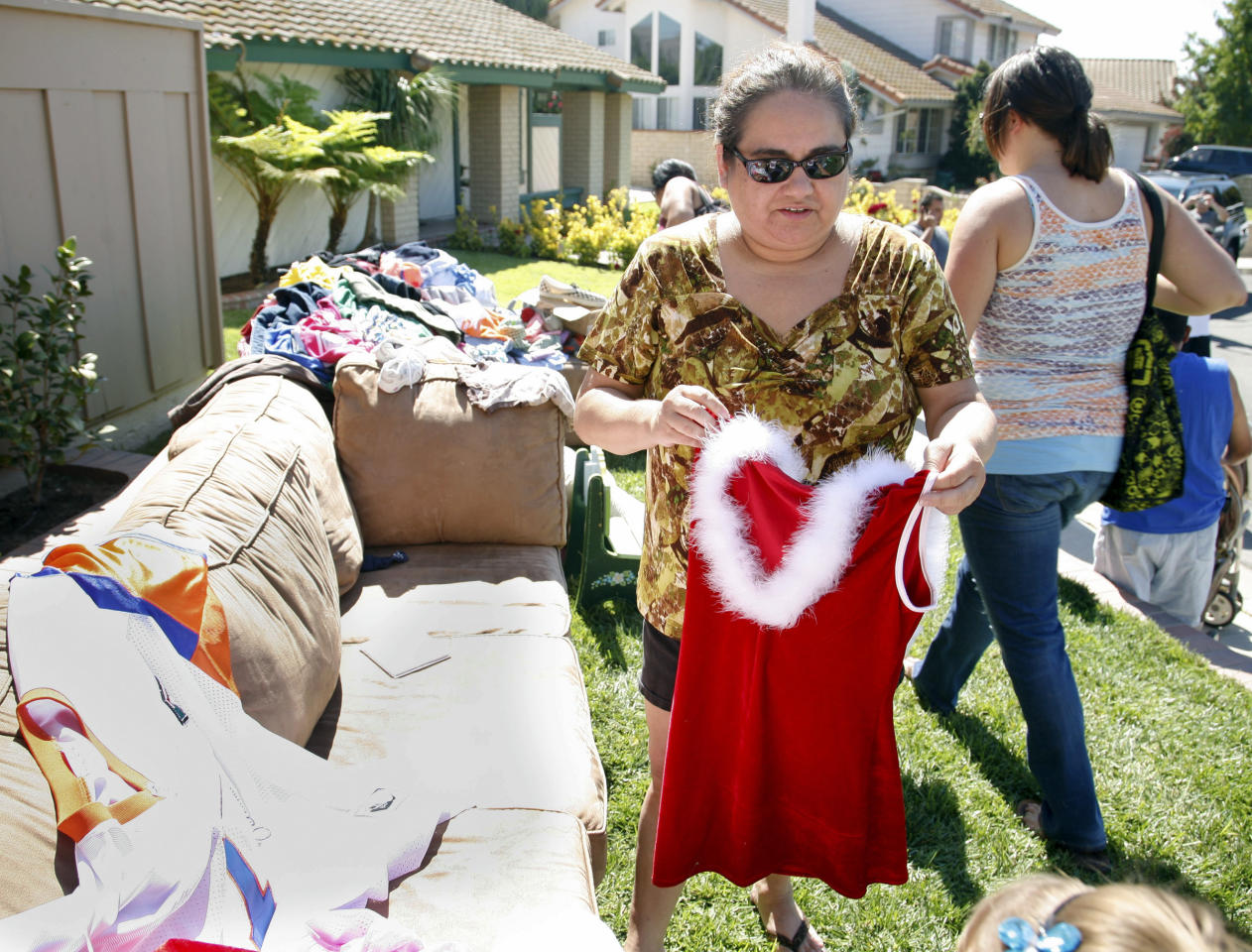 "FILE - This Sept, 25, 2010 file photo shows neighbor Cori Mahlen looking at an item of clothing at ""Octomom"" Nadya Suleman's yard sale and auction outside Suleman's home in La Habra, Calif. Suleman, the mother of octuplets, has been living in the home for nearly two years. The man who sold the home to Suleman says he is going ahead with eviction proceedings because she can't come up with a $450,000 balloon payment."