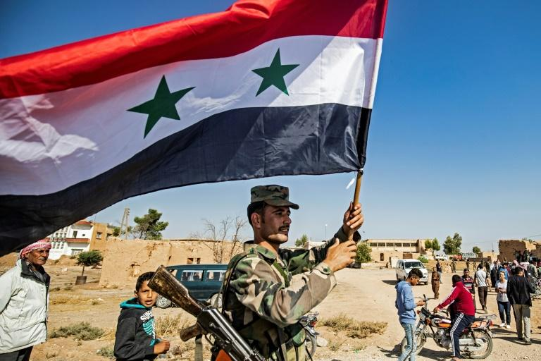A Syrian regime soldier waves the national flag in the town of Tal Tamr as Damascus deploys forces towards the Turkish border (AFP Photo/Delil SOULEIMAN)