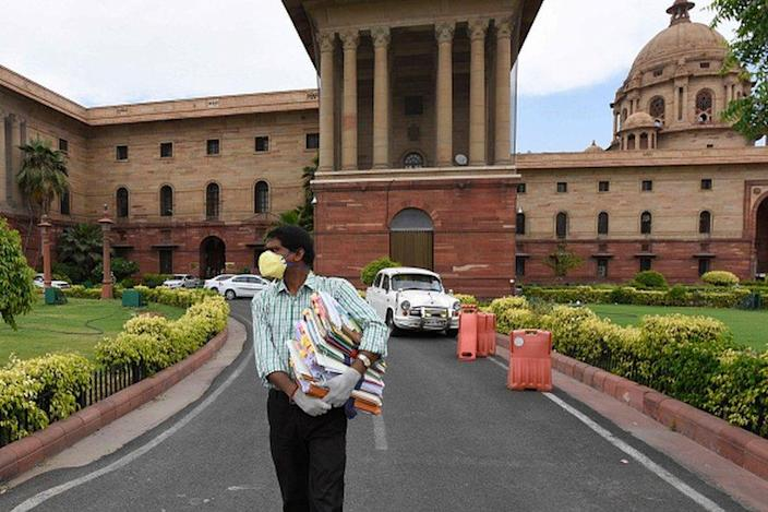 A government employee holding files as he comes out from Ministry of Finance at North Block as ministries and government offices partially resume working from office, at Raisina Hills on April 20, 2020 in New Delhi,