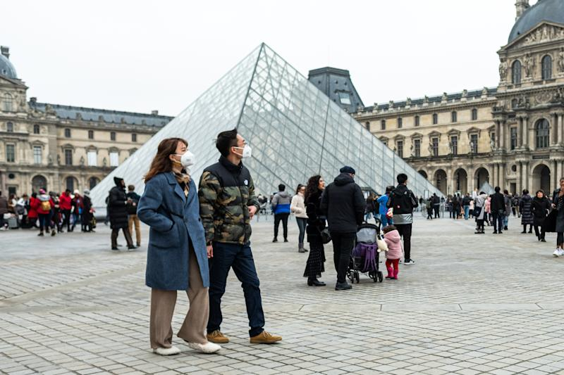 Chineese tourists wear face mask near the Louvre Museum in Paris, France, on 26 January 2020. (Photo by Jerome Gilles/NurPhoto via Getty Images)