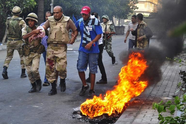 An Egyptian civilian (R) helps an army officer after he was wounded during clashes with supporters of the Muslim Brotherhood and ousted president Mohamed Morsi, in the northern Mediterranean city of Alexandria on August 16, 2013