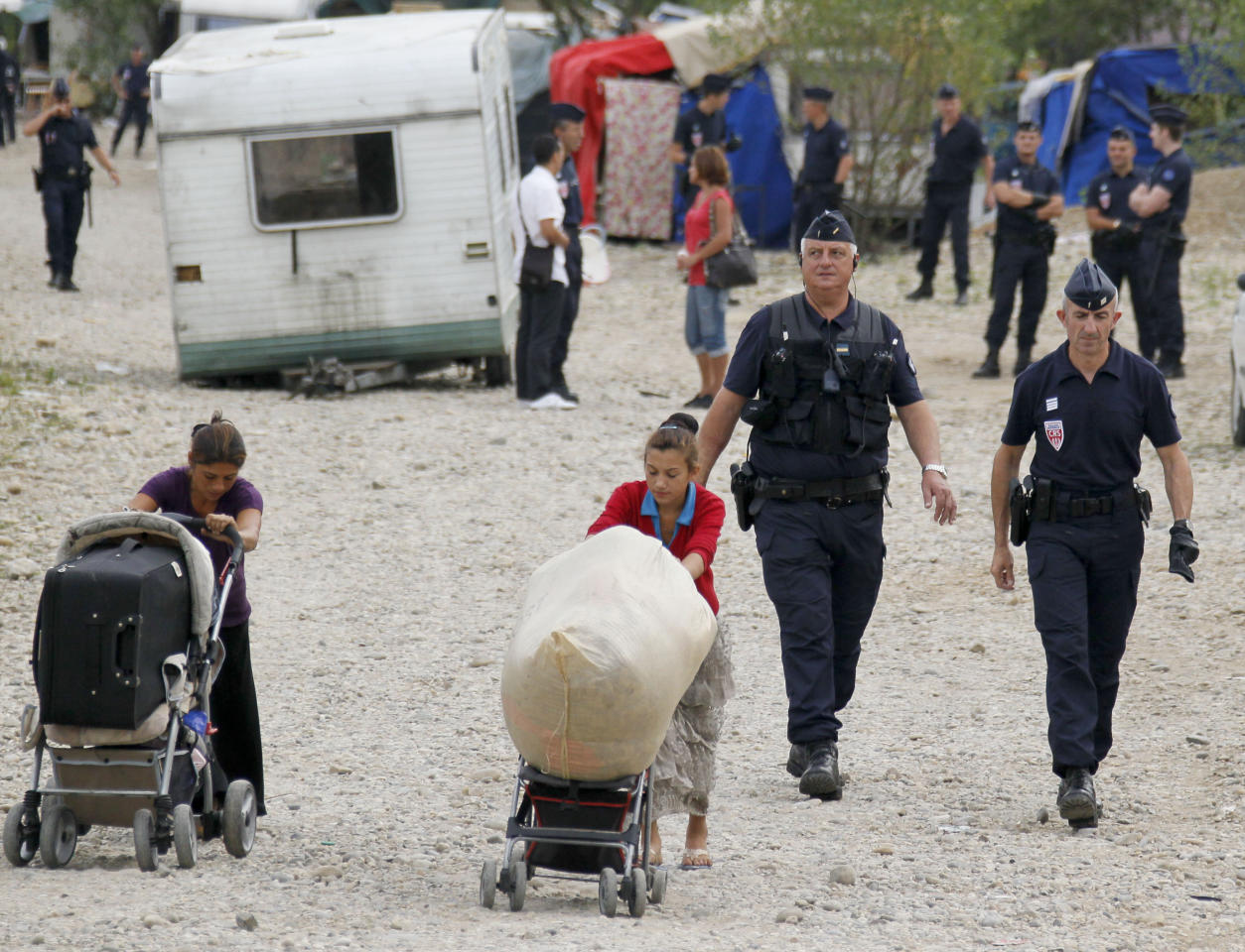 "French CRS police evacuate families and remove their caravans from an illegal camp housing about 114 Roma, referred to as ""Gens du Voyage"", in Saint-Priest, near Lyon, Southeastern France, August 28, 2012. The French Interior minister said on Monday he would ask Romania and Bulgaria to do more to integrate their Roma minorities as the new government in Paris grapples with how to handle Roma immigrants in France.   REUTERS/Robert Pratta   (FRANCE - Tags: SOCIETY IMMIGRATION POLITICS)"