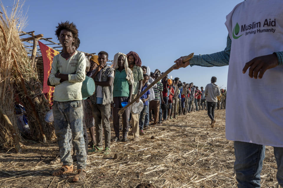 A worker for Muslim Aid organizes Tigrayan refugees waiting in line to receive cooked rice and lentils, at Umm Rakouba refugee camp in Qadarif, eastern Sudan, Saturday, Dec. 12, 2020. (AP Photo/Nariman El-Mofty)