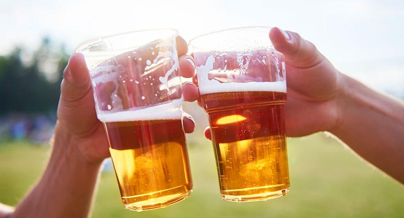 Two people hold beers in plastic cups.