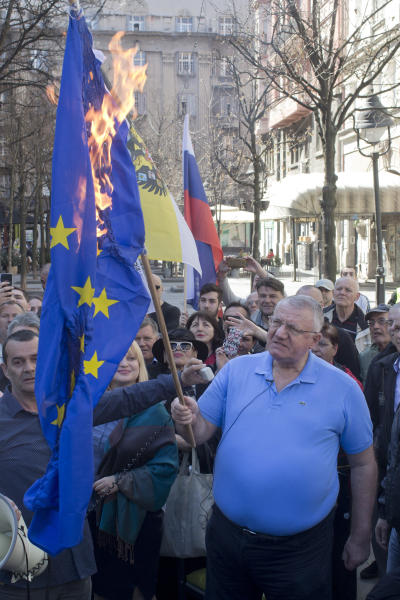 Vojislav Seselj, front, the leader of the ultranationalist Serbian Radical Party, holds a burning EU flag as he and others gather for a protest in Belgrade, Serbia, Sunday, March 24, 2019. Members of the ultranationalist Serbian Radical Party gathered for a protest on Sunday in the Serbian capital to mark the 20th anniversary of the NATO led bombing campaign against Serbia in 1999. (AP Photo/Marko Drobnjakovic)
