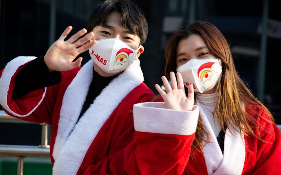 South Korean volunteers wearing Santa Claus costumes and face masks pose for a photograph as they attend a Christmas season charity event in Seoul, South Korea - JEON HEON-KYUN/EPA-EFE/Shutterstock