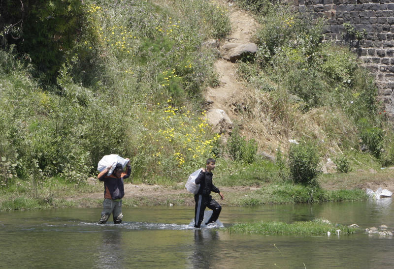 """Two Syrian men carry their belongings, to cross the border illegally through the river, as they flee from violence in Talkalakh in west Syria, in the Wadi Khaled area, about one kilometer (0.6 miles) from the Lebanon-Syria border, north Lebanon, Monday May 16, 2011. Carrying mattresses and bags of clothing, Syrians fleeing their homeland described a """"catastrophic"""" scene Monday in a besieged border town that has been largely sealed off as the army tries to crush a two-month uprising. (AP Photo/Bilal Hussein)"""