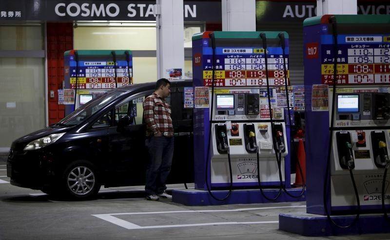A man stands to wait for refueling for his car at Cosmo Energy Holdings' Cosmo Oil service station in Tokyo