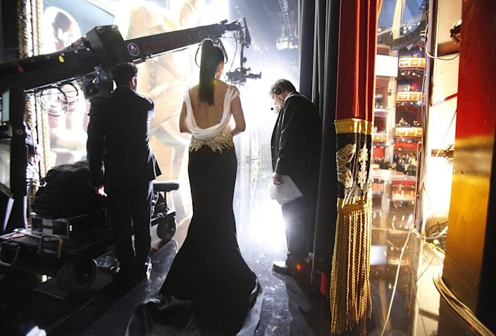 2012: Sandra Bullock waits with a tuxedoed stage assistant before going onstage