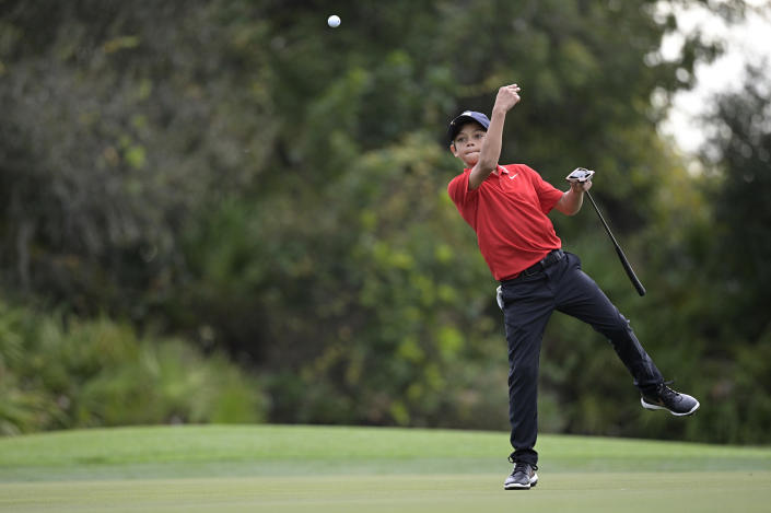 Charlie Woods, son of golfer Tiger Woods, tosses a ball to his caddie after marking his spot on the third green during the final round of the PNC Championship golf tournament, Sunday, Dec. 20, 2020, in Orlando, Fla. (AP Photo/Phelan M. Ebenhack)
